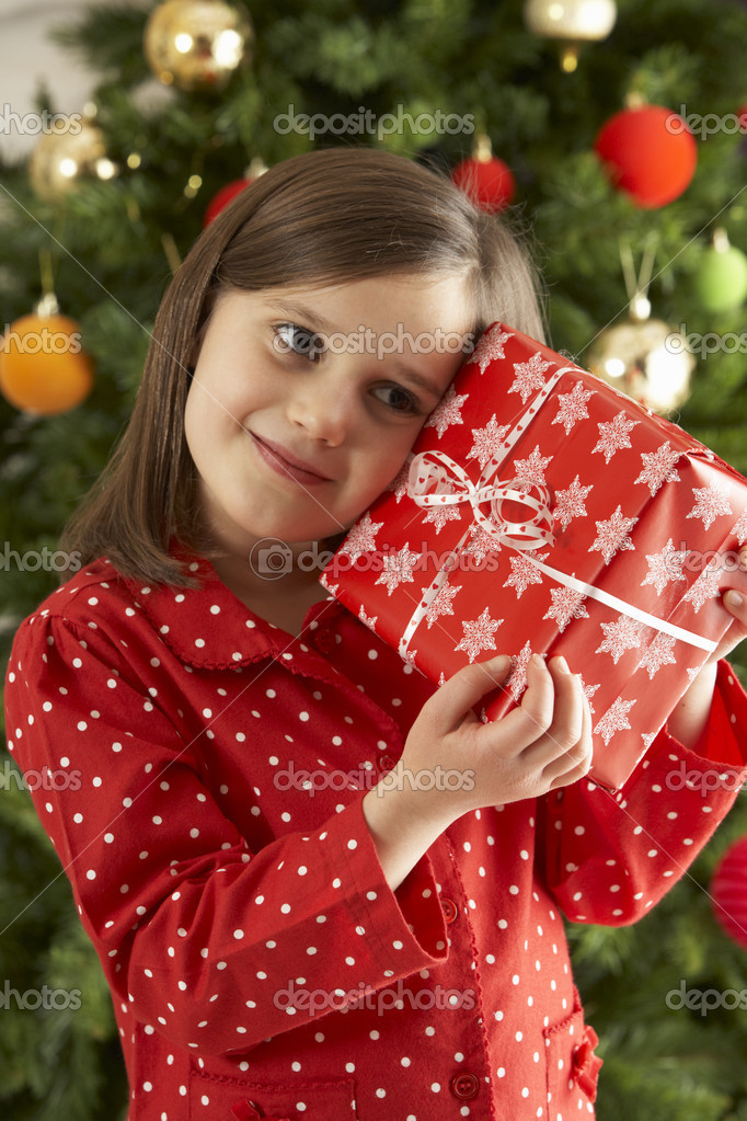 Young Girl Holding Gift In Front Of Christmas Tree — Stock Photo #4840982