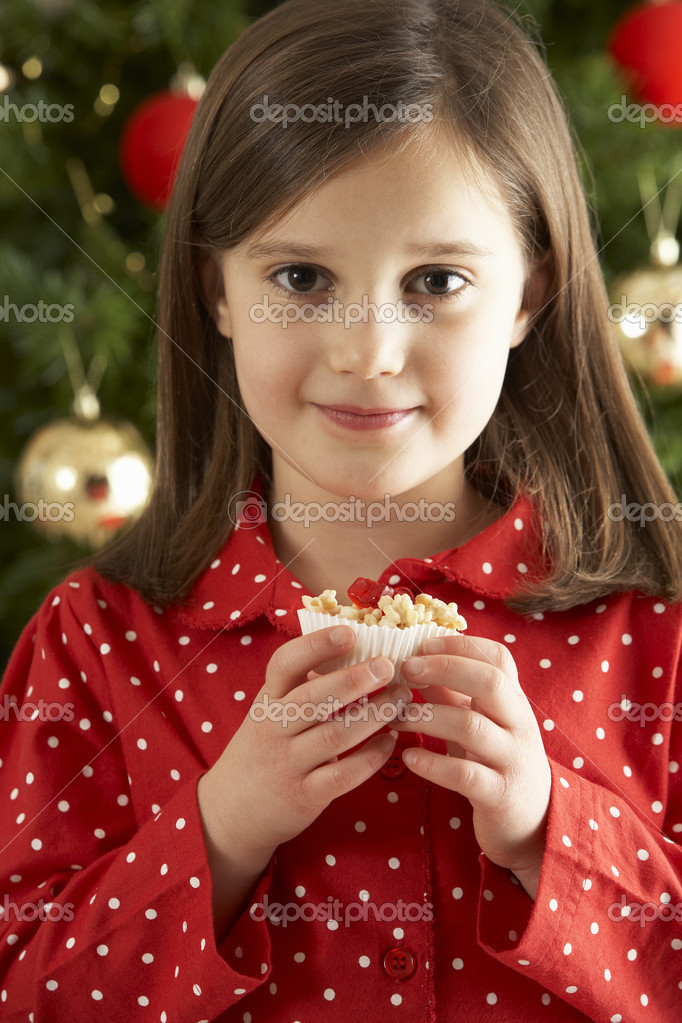 Young Girl Eating Reindeer Shaped Christmas Cookie In Front Of Christmas Tree — Stok fotoğraf #4840984