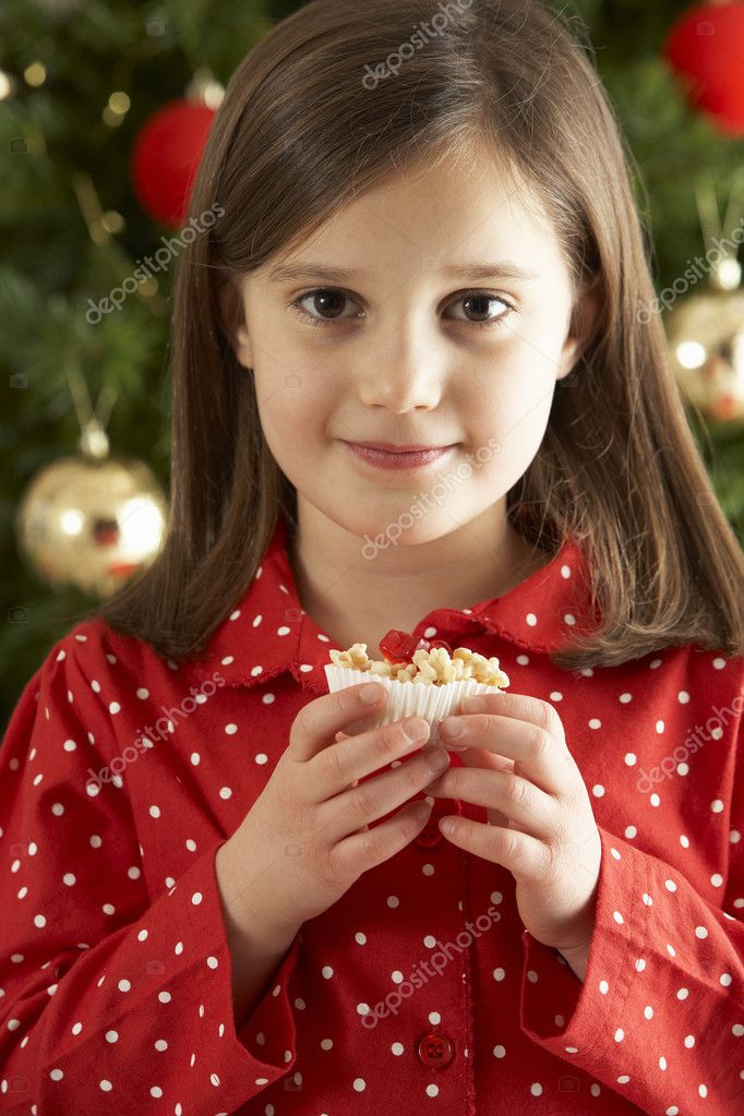 Young Girl Eating Reindeer Shaped Christmas Cookie In Front Of Christmas Tree — Stockfoto #4840984