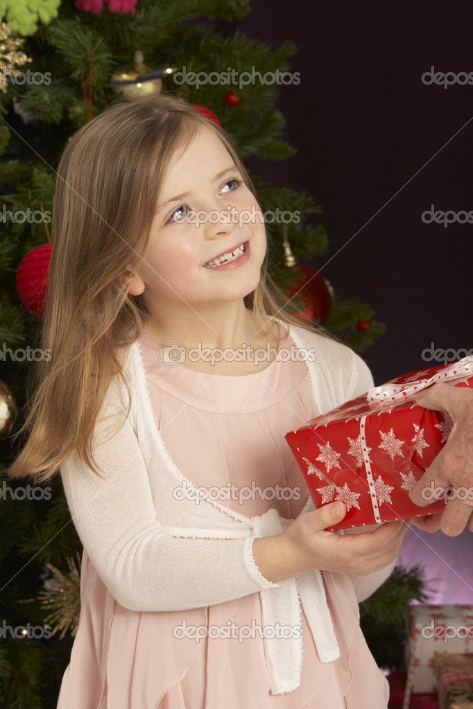 Young Girl Holding Christmas Present In Front Of Christmas Tree  Stock Photo #4840994
