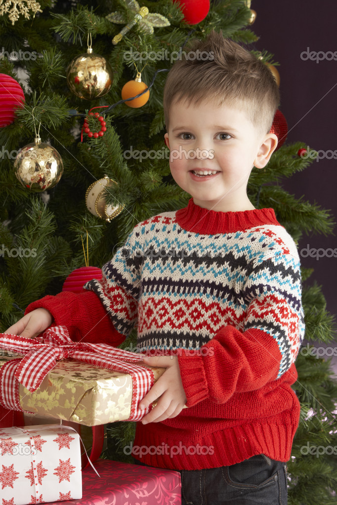 Young Boy Holding Wrapped Present In Front Of Christmas Tree — Stock Photo #4841000