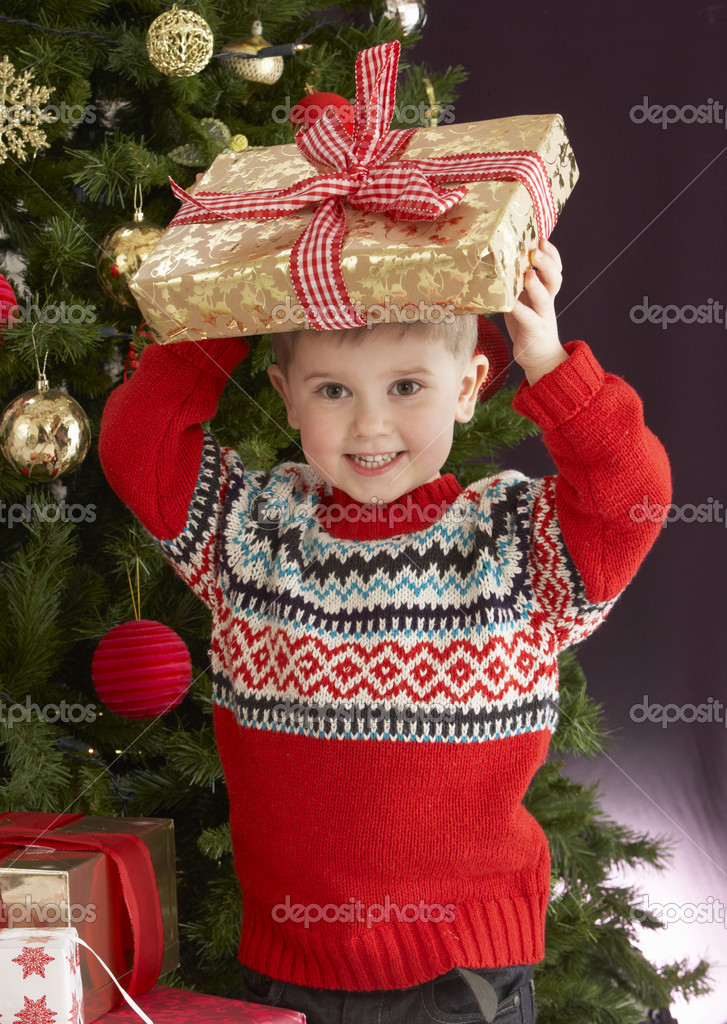 Young Boy Holding Christmas Present In Front Of Christmas — Foto Stock #4841002