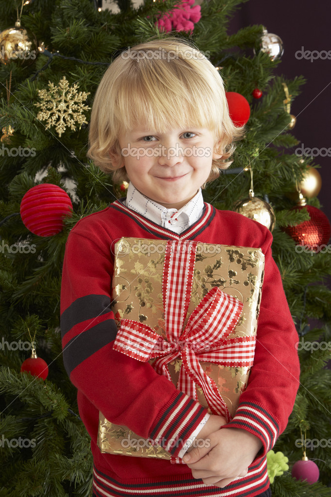 Young Boy Holding Christmas Present In Front Of Christmas — Stock Photo #4841008