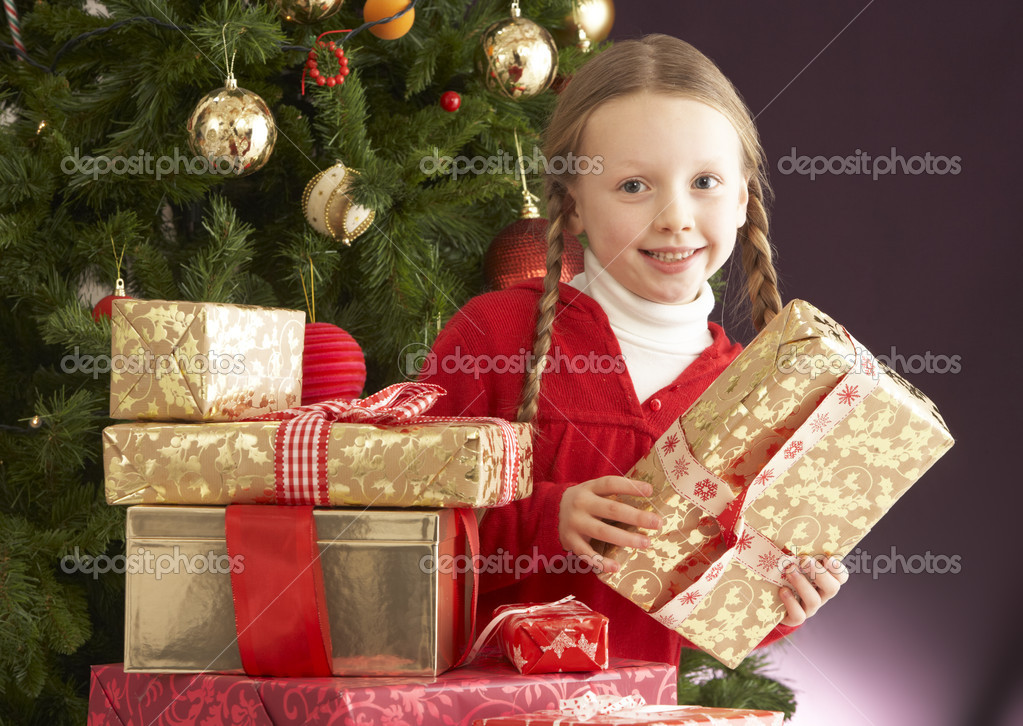 Young Girl Holding Christmas Present In Front Of Christmas Tree  Lizenzfreies Foto #4841024