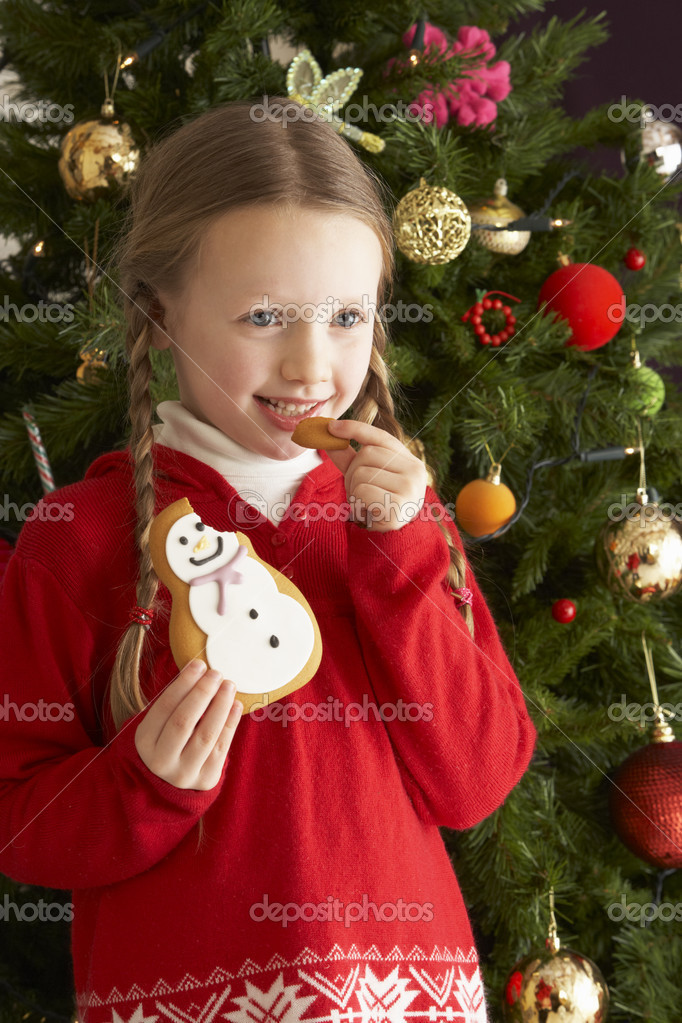 Young Girl Eating Cookie In Front Of Christmas Tree — Stok fotoğraf #4841032
