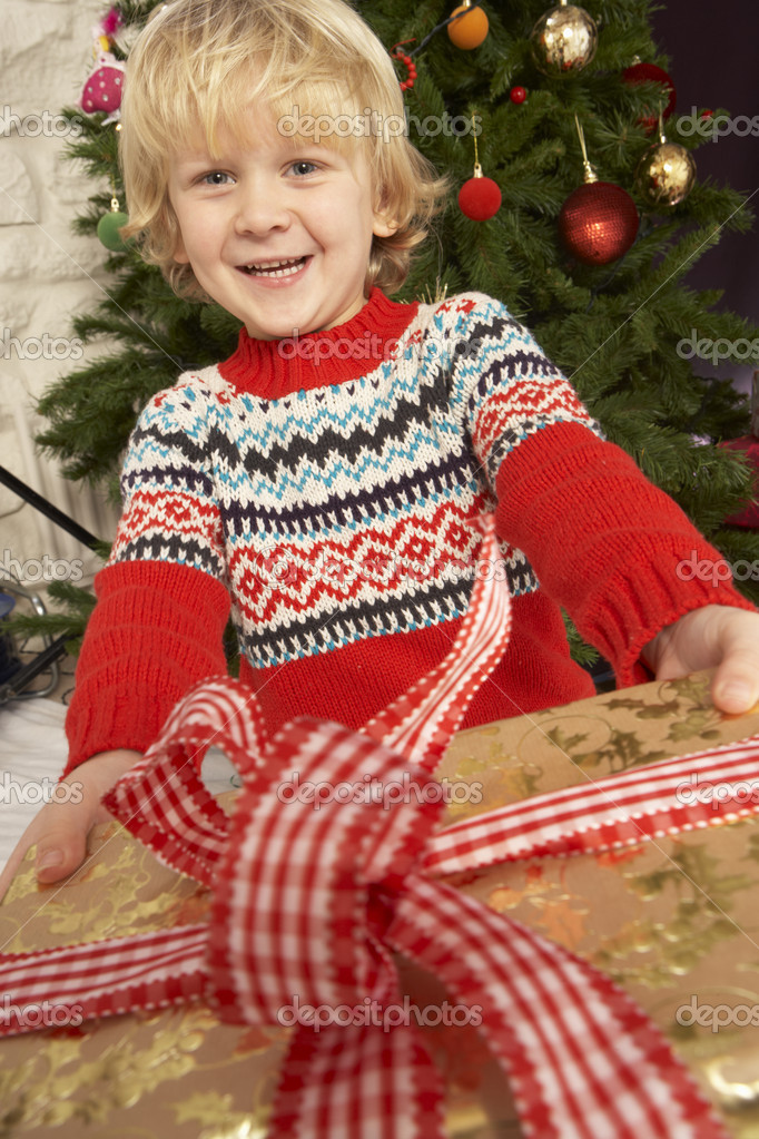 Young Boy Holding Gift In Front Of Christmas Tree — Stock Photo #4841064