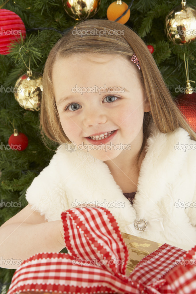 Young Girl Holding Christmas Present In Front Of Christmas Tree — Stock Photo #4841070