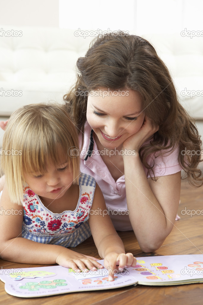 Mother and daughter learning to read at home stock photo