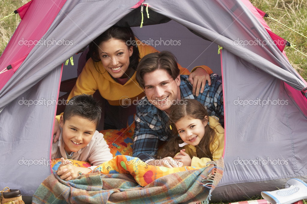 Young Family Relaxing Inside Tent On Camping Holiday — Stock Photo #4842048