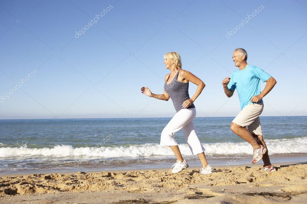 Senior Couple In Fitness Clothing Running Along Beach — Stock Photo #4843176