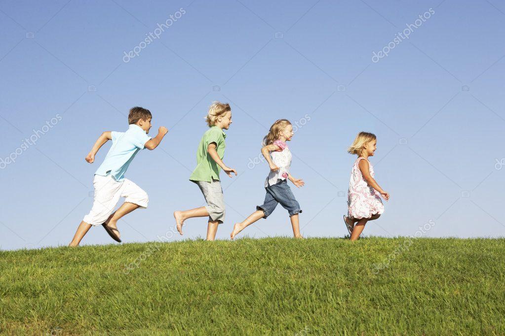 Young children running through field stock image