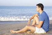 Man sitting on beach relaxing — Stock Photo