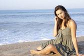 Mujer sentada en la playa relajante — Foto de Stock