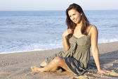 Woman sitting on beach relaxing — Stockfoto
