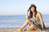 Woman sitting on beach relaxing — Stock Photo