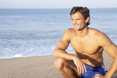 Man sits on beach relaxing — Stock Photo