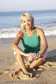 Senior woman sitting on beach relaxing — Stock Photo