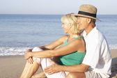 Senior couple sitting on beach relaxing — Stock Photo
