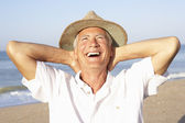 Senior man sitting on beach relaxing — Stock Photo