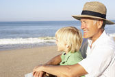 Grandfather with child on beach relaxing — Stock Photo