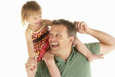 Young man carries child on shoulders — Stock Photo