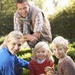 Young family sit together in garden — Foto Stock