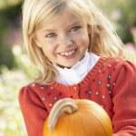 Young girl posing with pumpkin in garden — Stock Photo