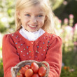 Young girl posing with tomatoes in garden — Stock Photo #5184094