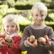 Young children in garden pose with vegetables — Stock Photo