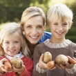 Young mother and children in garden pose with vegetables — Stok fotoğraf
