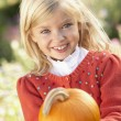 Foto Stock: Young girl posing with pumpkin in garden