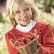 Young girl posing with tomatoes in garden — Stock Photo #5189897