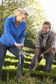 Young couple working in garden — Stock Photo