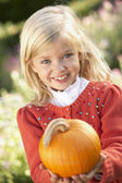 Young girl posing with pumpkin in garden — Stok fotoğraf