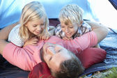 Young father plays with children in tent — Stock Photo