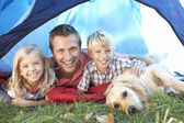 Young father poses with children in tent — Stock Photo