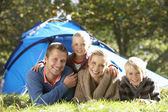 Young family poses outside of tent — Stockfoto