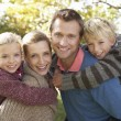Young family pose in park — Stock Photo