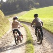 Two young children ride bicycles in park — Stock Photo #5190505