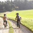 Two young children ride bicycles in park — Stock Photo #5190508