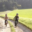 Two young children ride bicycles in park — Stock Photo