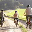 Young father with children ride bikes in park — Stock Photo