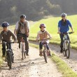 Young parents with children ride bikes in park — Stockfoto