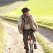 Young man rides his bike in park — Stock Photo