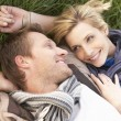 Young couple lying together on grass — Stock Photo #5190596