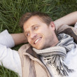 Young man lying alone on grass — Stock Photo