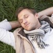 Young man napping alone on grass — Stock Photo