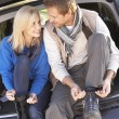 Young couple tie boots at rear of car - Stock Photo