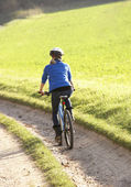 Mladá žena jezdí na kole v parku — Stock fotografie