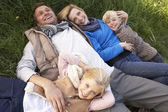 Young family lying together on grass — Stock Photo